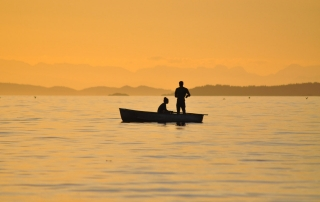 two men in a boat fishing during sunset