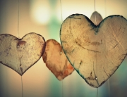 three wood heart shapes and bokeh background